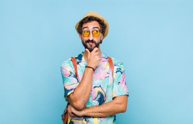 若いひげを生やした観光客の男性は、さまざまなオプションで、疑わしくて混乱していると感じ、どの決定を下すか疑問に思っています
