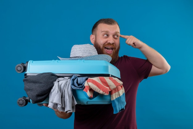 Young bearded traveler man holding suitcase full of clothes looking aside pointing temple having new idea