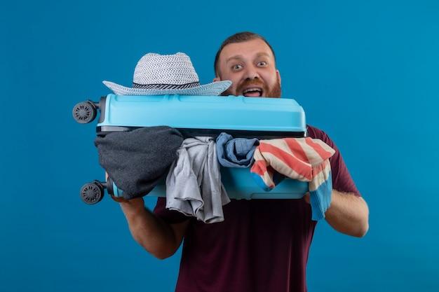 Uomo giovane viaggiatore barbuto che tiene la valigia piena di vestiti gridando in preda al panico emotivo e preoccupato