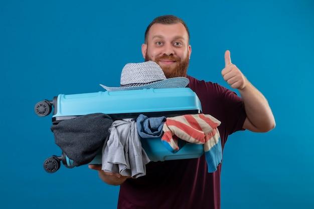 楽観的で幸せな笑顔が親指を見せて服でいっぱいのスーツケースを持っている若いひげを生やした旅行者の男