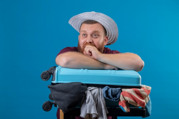 Молодой бородатый путешественник в летней шляпе с чемоданом, полным одежды, оптимистичный и счастливый улыбающийся, смотрящий в сторону с задумчивым выражением лица