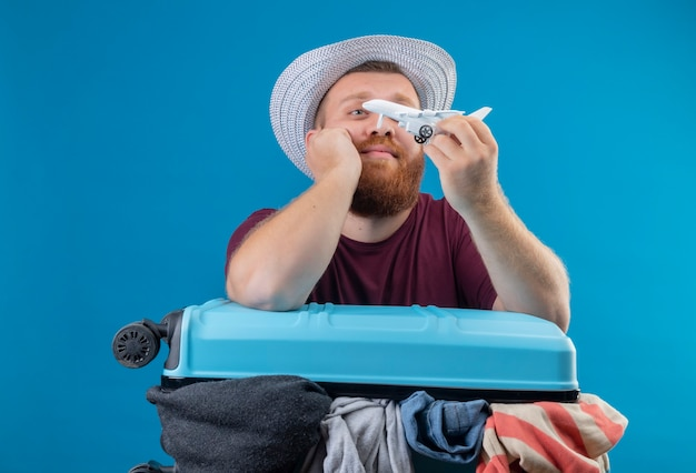 Young bearded traveler man in summer hat  with suitcase full of clothes holding toy airplane playful optimistic and happy smiling looking aside with dreamy look