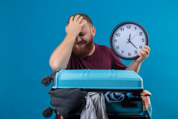 Young bearded traveler man  with suitcase full of clothes holding wall clock touching his head for mistake looking confused