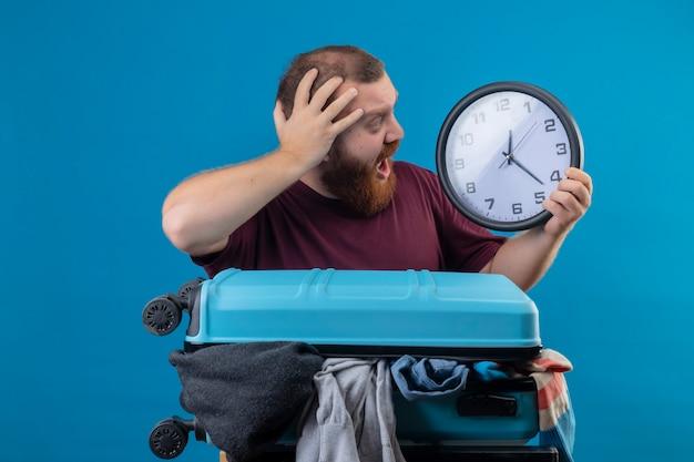 Uomo giovane viaggiatore barbuto con la valigia piena di vestiti che tengono l'orologio di parete che tocca la sua testa nel panico