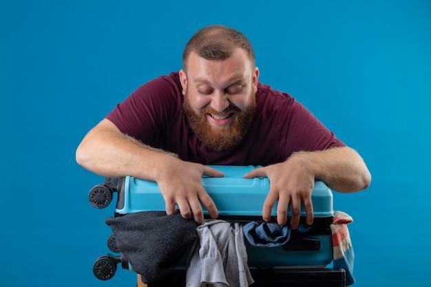 Uomo giovane viaggiatore barbuto con la valigia piena di vestiti che sembra infastidito cercando di chiudere la sua valigia