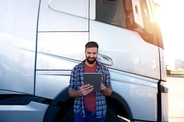 Молодой бородатый дальнобойщик проверяет свой маршрут на планшетном компьютере с диспетчером и стоит у длинного автомобиля.