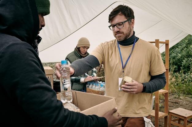 깡통을 들고 상자가 있는 노숙자에게 물 한 병을 주는 안경을 쓴 젊은 수염 자원 봉사자