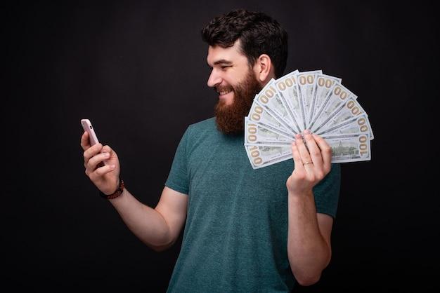 그의 전화에 내기를 하는 젊은 수염 남자는 그의 손에 많은 돈을 들고 있다.
