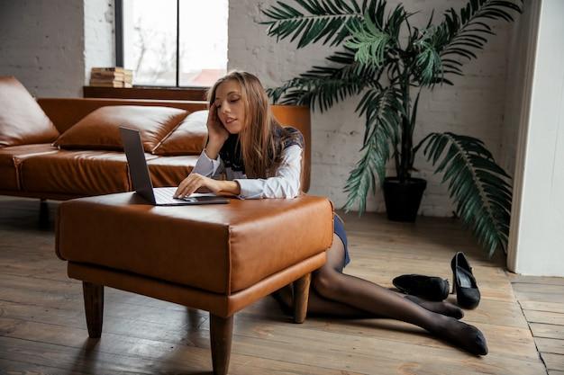 若い美しさのエレガントなビジネスウーマンは彼女の靴を脱いで、ラップトップで自宅で仕事をします。高品質の写真