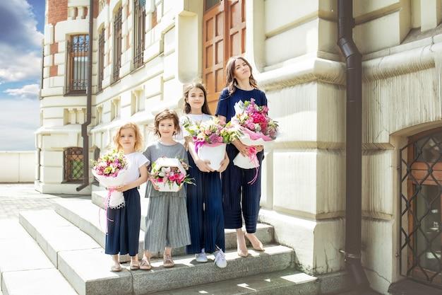 若い美しい大人の母親と花の花束を持つ彼女の小さな陽気で幸せな娘