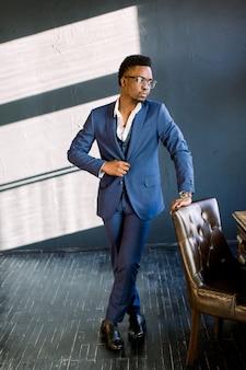 椅子に手を置くオフィスでスタイリッシュなスーツ立っている若い美しいアフリカ系アメリカ人の男