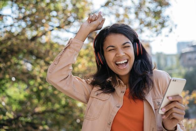ヘッドフォンで音楽を聴いたり、踊ったり、歌を歌ったりする若い美しいアフリカ系アメリカ人女性