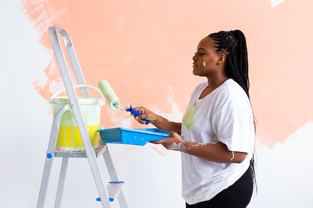 Young beautiful african american woman painting wall in her new apartment. renovation and