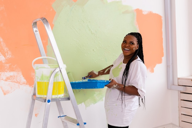 Young beautiful african american woman painting wall in her new apartment