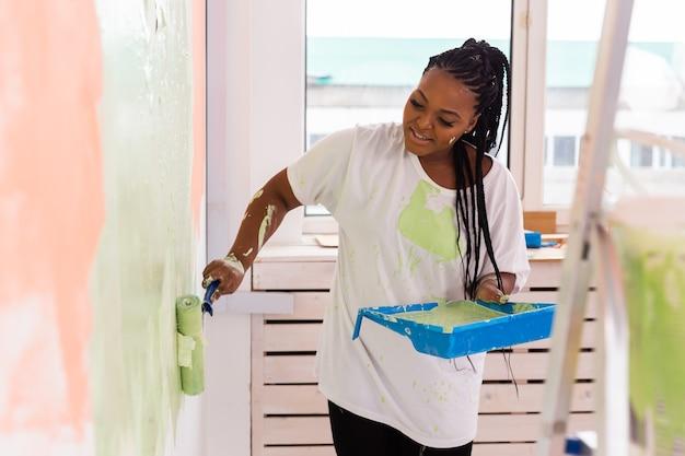 그녀의 새 아파트에서 젊은 아름 다운 아프리카 계 미국인 여자 그림 벽. 리노베이션 및