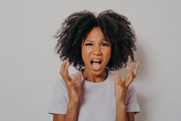 カジュアルなtシャツを着て、怒って怒って立って、怒りで叫びながら欲求不満と激怒の手を上げて、巻き毛の若い美しいアフリカ系アメリカ人女性。怒りと攻撃的なコンセプト