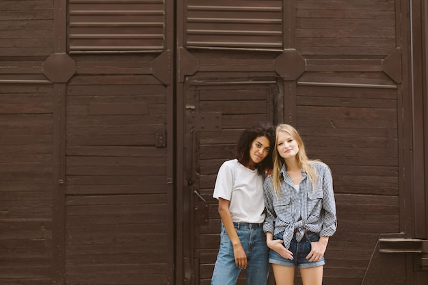 Young beautiful african american woman with dark curly hair in t-shirt and jeans and pretty woman with blond hair in shirt and denim shorts dreamily  with brown wall