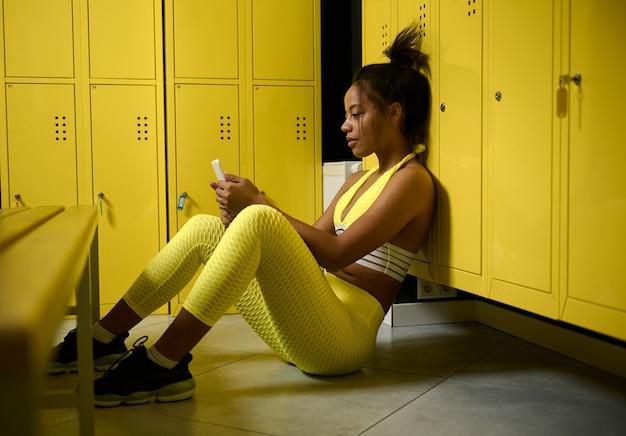 젊고 아름다운 아프리카 여성 운동선수, 꽉 끼는 노란색 운동복을 입은 스포츠 여성은 라커룸 바닥에 앉아 휴대전화를 긁고 있습니다. 운동 후 휴식을 취하는 스포티한 여성