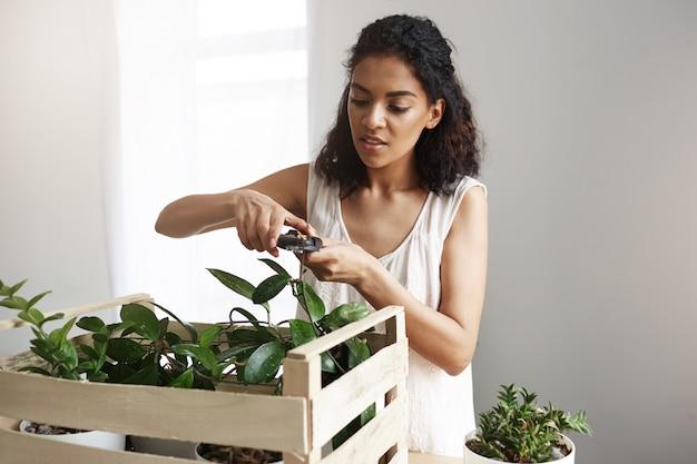 職場で若い美しいアフリカ女性植物学者切削植物茎。スペースをコピーします。