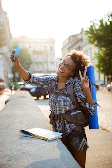 笑みを浮かべて、selfieを作るバックパックと若い美しいアフリカ女性旅行者。