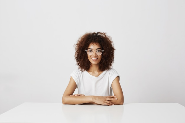 Young beautiful african girl in glasses smiling  sitting over white wall