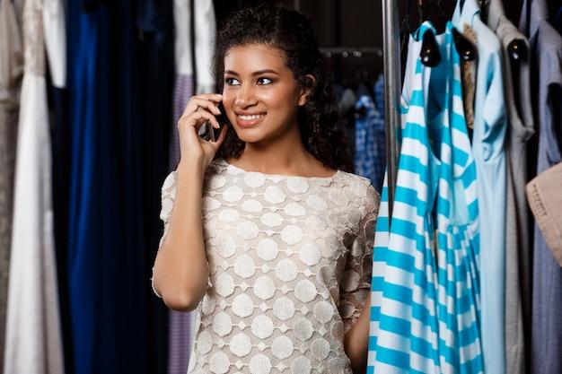 Молодая красивая девушка африканских, выступая на телефоне в торговом центре.