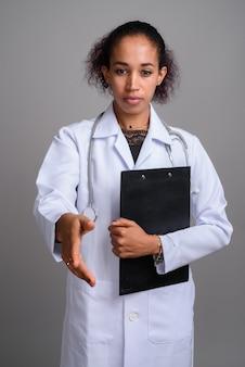 Молодая красивая африканская женщина-врач у серой стены