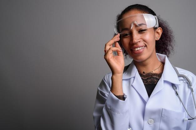 灰色の壁に対して若い美しいアフリカの女性医師