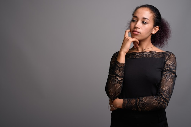 Молодая красивая африканская женщина на сером