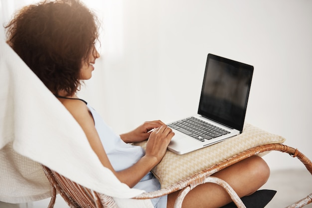 Young beautiful african woman in profile smiling sitting with laptop in chair working on her diploma.