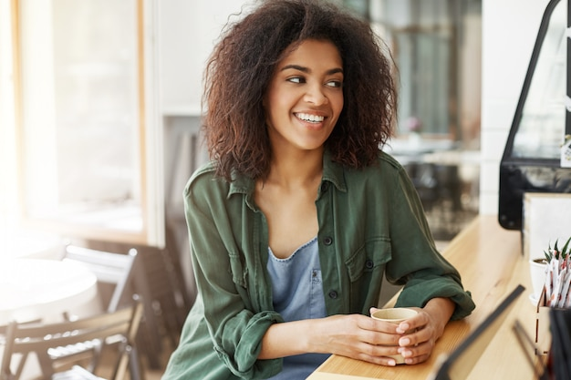 若い美しいアフリカ女性学生リラックスしたカフェに座ってリラックスしてコーヒーを飲みながら休憩します。