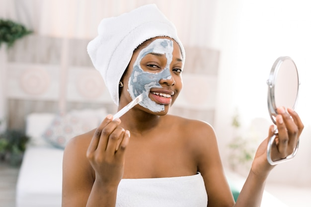 Young beautiful african woman in white towel applying face mask and holding the mirror. spa skin care concept