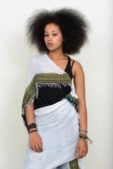白の伝統的な服でアフロの髪を持つ若い美しいアフリカの女性