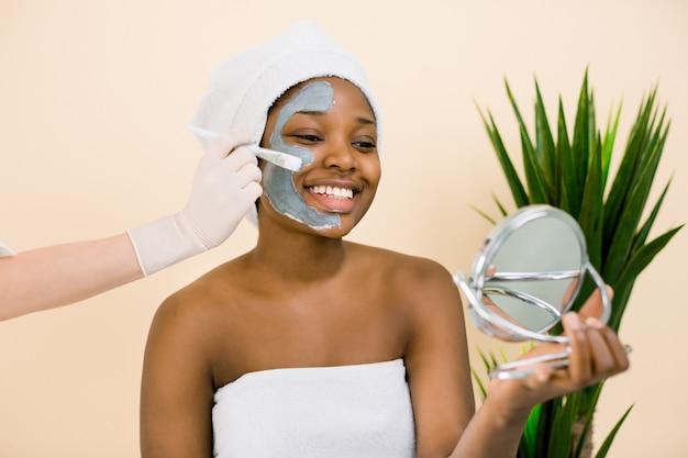 鏡で見ている顔のマスク、頭の上の白いタオルで若いアフリカ美女