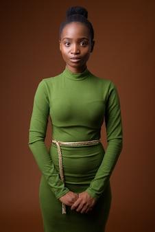 Молодая красивая африканская бизнесвумен зулус против коричневого backgro