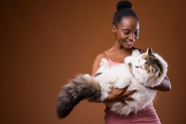 Молодая красивая женщина африканских зулусов, держащая кошку, улыбаясь