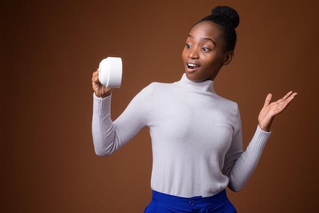 커피 컵을 들고 젊은 아름 다운 아프리카 줄 루어 여자