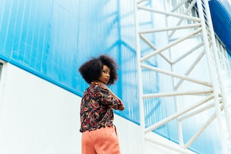 Young beautiful afro-american woman posing in colorful stylish clothes, outdoors.