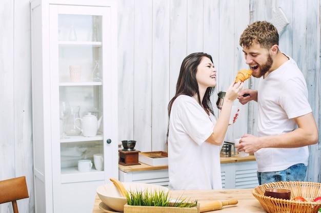 아침에 부엌에서 아침을 하는 아름답고 행복한 젊고 행복한 커플 남녀