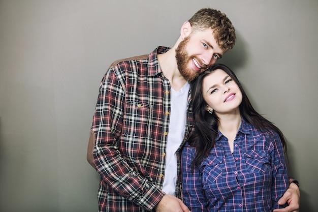 회색 배경에 껴안고 웃고 있는 젊고 아름다운 행복한 커플 남녀
