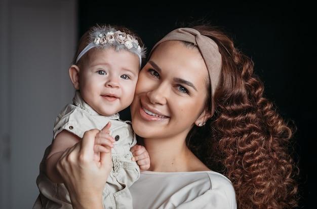 彼女の腕の中で赤ん坊の娘を持つ若い美しく幸せな母親。家族写真