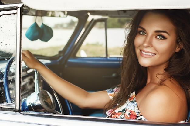 레트로 컨버터블 자동차를 운전하는 젊고 아름답고 행복한 여자