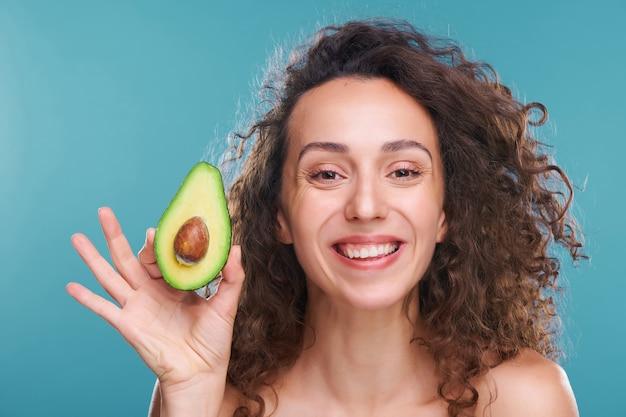 Молодая красивая и радостная женщина с роскошными вьющимися волосами смотрит на вас с зубастой улыбкой, держа в руке половину свежего авокадо