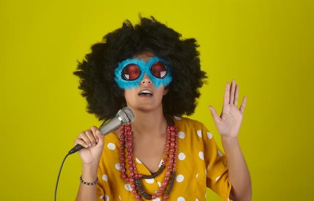 カーリーアフロの髪型と黄色の壁にマイクを使って歌う面白い眼鏡の美しい笑顔の少女
