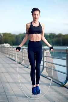 Молодая красивая и сильная женщина активно занимается с веревкой летом в парке. спортивная концепция. здоровый образ жизни