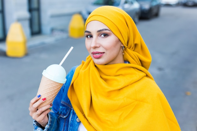 Young beautiful arab woman in hijab drinking cooling cocktail outdoor.