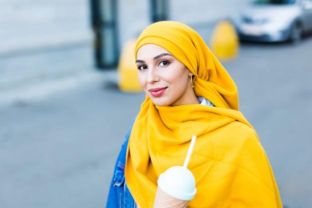 屋外で冷却カクテルを飲むヒジャーブの若い美しいアラブの女性。