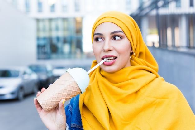 Молодая красивая арабская женщина в хиджабе, пить охлаждающий коктейль на открытом воздухе.