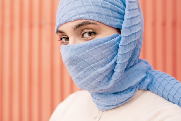 Young beautiful arabian female with her face hidden behind blue hijab looking at you in isolation