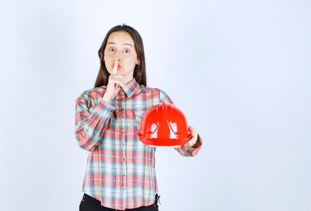 Молодая красивая женщина архитектора держа шлем безопасности и делая знак тишины.